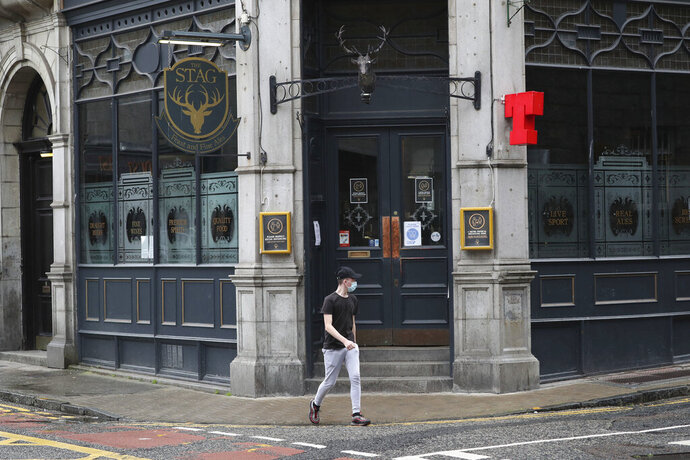 A man walks past the closed Stag pub, after bars, cafes and restaurants were ordered to close as lockdown restrictions were reimposed due to a coronavirus cluster in the area, in Aberdeen, Scotland, Wednesday, Aug. 5, 2020.  A five-mile travel rule has been put in place and residents are being told not to enter each other's houses as First Minister Nicola Sturgeon said over 50 cases have now been reported. (Andrew Milligan/PA via AP)