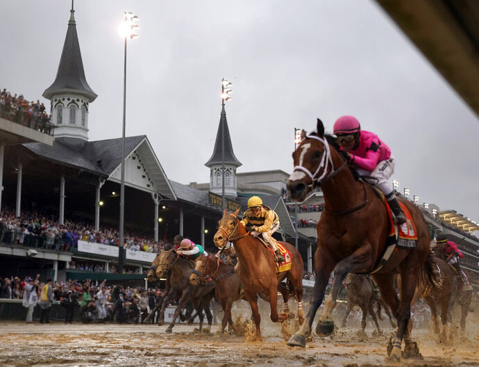 FILE - In this May 4, 2019, file photo, Luis Saez rides Maximum Security, right, across the finish line first against Flavien Prat on Country House during the 145th running of the Kentucky Derby horse race at Churchill Downs in Louisville, Ky. Churchill Downs says the rescheduled Kentucky Derby and Oaks will run this fall with spectators under strict guidelines to limit crowd density for the race that annually attracts more than 100,000. The 146th runnings of the Oaks for fillies and the Derby were postponed from May 1-2 to Sept. 4-5 because of the coronavirus pandemic. Fans will be encouraged to wear masks at all times unless seated and to practice social distancing. (AP Photo/Matt Slocum, File)