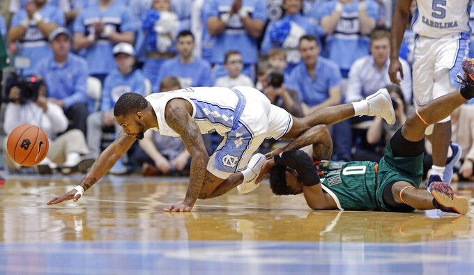 North Carolina's Seventh Woods, left, and Miami's Chris Lykes (0) fall to the floor chasing the ball during the first half of an NCAA college basketball game in Chapel Hill, N.C., Saturday, Feb. 9, 2019. (AP Photo/Gerry Broome)