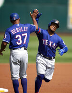 Texas Rangers' Willie Calhoun, right, gets a high-five from third base coach Tony Beasley (37) after hitting a solo home run off Oakland Athletics starting pitcher Tanner Roark during the first inning of a baseball game Sunday, Sept. 22, 2019, in Oakland, Calif. (AP Photo/D. Ross Cameron)