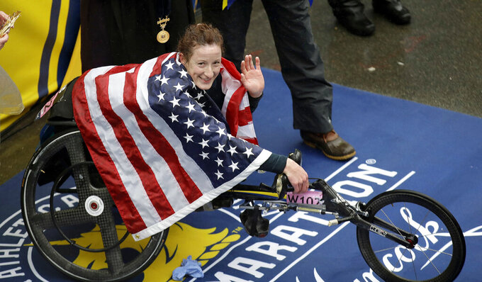 """FILE - In this April 16, 2018, file photo, Tatyana McFadden, of the United States, celebrates after winning the women's wheelchair division of the 122nd Boston Marathon, in Boston. McFadden is among several Paralympic athletes who are profiled in the Nexflix documentary """"Rising Phoenix"""" that will be released in 190 countries on Wednesday, Aug. 26, 2020.(AP Photo/Charles Krupa, File)"""