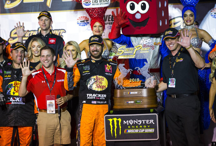 Martin Truex Jr. is presented with the trophy after winning a NASCAR Cup Series auto race at the Las Vegas Motor Speedway on Sunday, Sept. 15, 2019. (AP Photo/Chase Stevens)