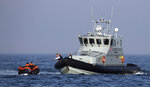 A Border Force vessel assist a group of people thought to be migrants on board from their inflatable dinghy in the Channel, Monday Aug. 10, 2020. A Royal Air Force surveillance plane is flying over the English Channel as the British government tries to curb the number of people crossing from France in small boats. Britain's Conservative government has talked tough amid a surge in the number of migrants crossing the Channel during recent warm summer weather. (Gareth Fuller/PA via AP)