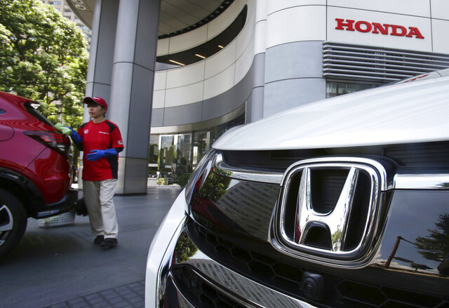 FILE - This July 31, 2018 file photo, shows an employee of Honda Motor Co. cleaning a Honda car displayed at its headquarters in Tokyo.  Honda has reached an $85 million settlement, Tuesday, Aug. 25, 2020,  with multiple states over allegations that it hid safety failures in the airbags of certain Honda and Acura vehicles sold in the U.S. The settlement ties up an investigation into Honda's alleged failure to inform regulators and consumers of issues related to the significant risk of rupture in the frontal airbag systems installed in certain cars, which could cause metal fragments to fly into the passenger compartments.  (AP Photo/Koji Sasahara, File)