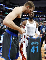 Dallas Mavericks' Dirk Nowitzki left, and Miami Heat's Dwyane Wade, second from right, talk as they swap jerseys after an NBA basketball game in Dallas, Wednesday, Feb. 13, 2019. (AP Photo/Tony Gutierrez)