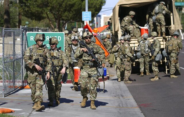 Arizona National Guard troops disembark from military vehicles near the Arizona Capitol on Tuesday, June 2, 2020, in Phoenix, where there have been several days of protests over the death of George Floyd, who died May 25 after being restrained by Minneapolis police. (AP Photo/Ross D. Franklin)