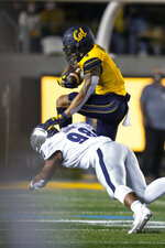 California wide receiver Nikko Remigio (4) hurdles Nevada defensive end Sam Hammond (98) during the first quarter of an NCAA college football game Saturday, Sept. 4, 2021, in Berkeley, Calif. (AP Photo/D. Ross Cameron)