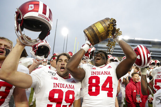 Indiana tight end Turon Ivy Jr. (84) and place kicker Nathanael Snyder (99) celebrate with the Old Oaken Bucket following an NCAA college football game against Purdue in West Lafayette, Ind., Saturday, Nov. 30, 2019. Indiana defeated Purdue 44-41 in double overtime. (AP Photo/Michael Conroy)
