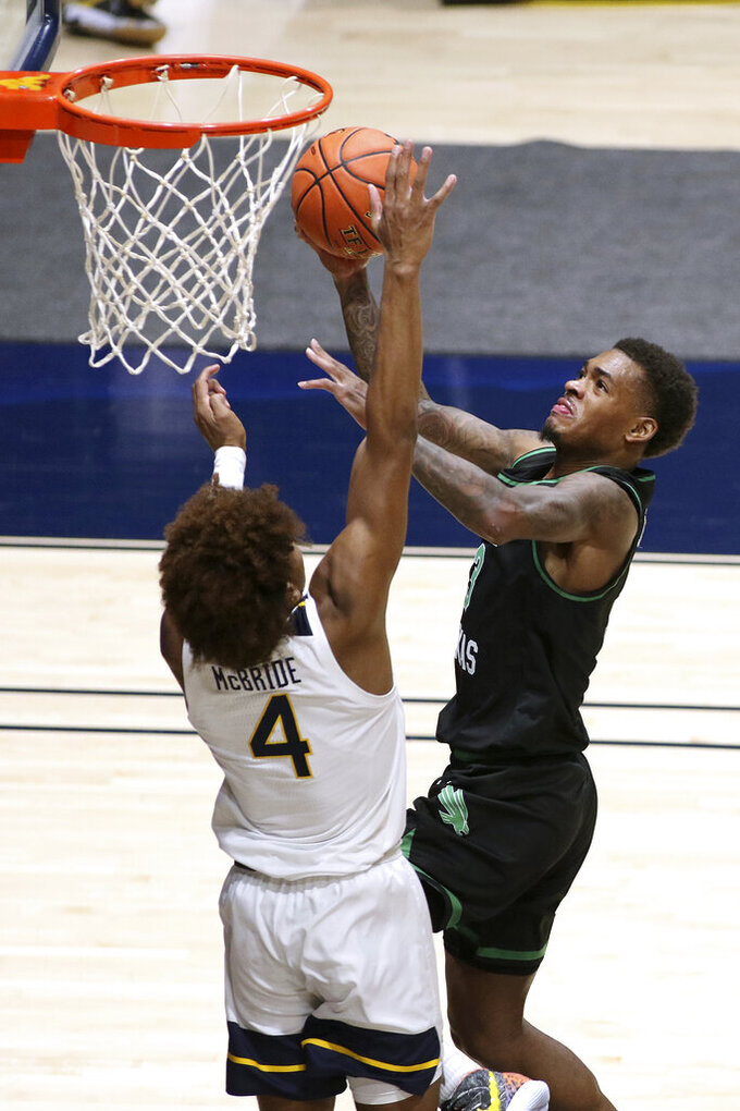 North Texas guard Javion Hamlet (3) shoots while defended by West Virginia guard Miles McBride (4) during the second half of an NCAA college basketball game Friday, Dec. 11, 2020, in Morgantown, W.Va. (AP Photo/Kathleen Batten)