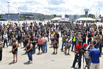 People stand in silence during a memorial and remembrance service for seven motorcyclists and their spouses who died in the June crash, Saturday, July 13, 2019 in the parking lot of Gillette Stadium in Foxboro, Mass. The seven bikers were killed when a pickup truck hauling a flatbed trailer slammed into a group of riders in Randolph, N.H.  (Mark Stockwell/The Sun Chronicle via AP)
