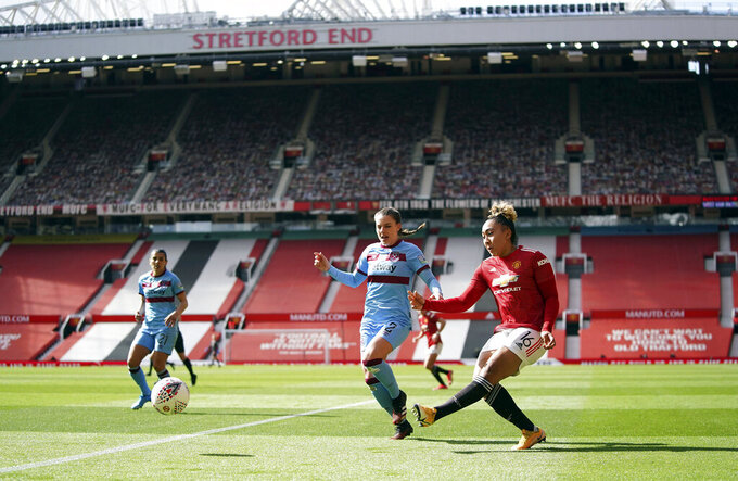 Manchester United's Lauren James, right, shoots during the Women's Super League match against West Ham at Old Trafford, Manchester, England, Saturday, March 27, 2021. The Manchester United women's team has made its Old Trafford debut in a league game against West Ham. The team normally plays its Women's Super League home matches at Leigh Sports Village but switched to Old Trafford during the international break in the men's game.  (Zac Goodwin/PA via AP)