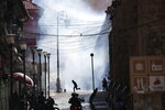 A supporter of former President Evo Morales is silhouetted against a wall of tear gas as he runs from advancing security forces during clashes in La Paz, Bolivia, Nov. 15, 2019. (AP Photo/Natacha Pisarenko)