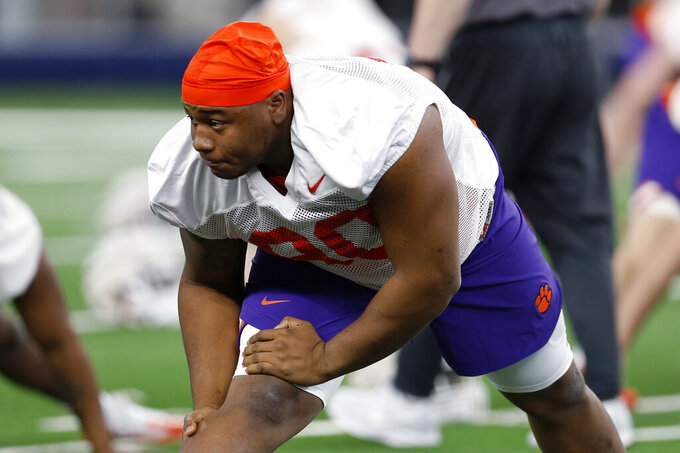 FILE - In this Dec. 24, 2018, file photo, Clemson defensive tackle Dexter Lawrence stretches during team practice at AT&T Stadium in Arlington, Texas. Galloway is seeing shorter lines at fast-food restaurants and fewer people around campus after Clemson started the fall semester with online-only undergraduate classes amid the coronavirus pandemic. Welcome to some Atlantic Coast Conference schools' version of campus bubbles — fewer people, reduced interactions — in an attempt to minimize outbreaks while resuming classes and launching a football season that looked in doubt much of the summer. (AP Photo/Jim Cowsert, File)