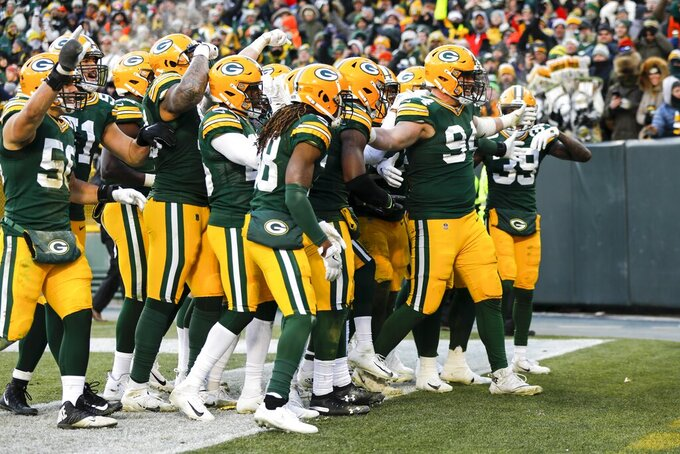 Green Bay Packers' Dean Lowry celebrates his interception with teammatesduring the second half of an NFL football game against the Chicago Bears Sunday, Dec. 15, 2019, in Green Bay, Wis. (AP Photo/Mike Roemer)