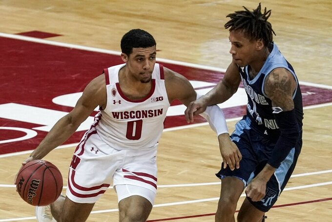 Wisconsin's D'Mitrik Trice drives past Rhode Island's Fatts Russell during the second half of an NCAA college basketball game Wednesday, Dec. 9, 2020, in Madison, Wis. (AP Photo/Morry Gash)
