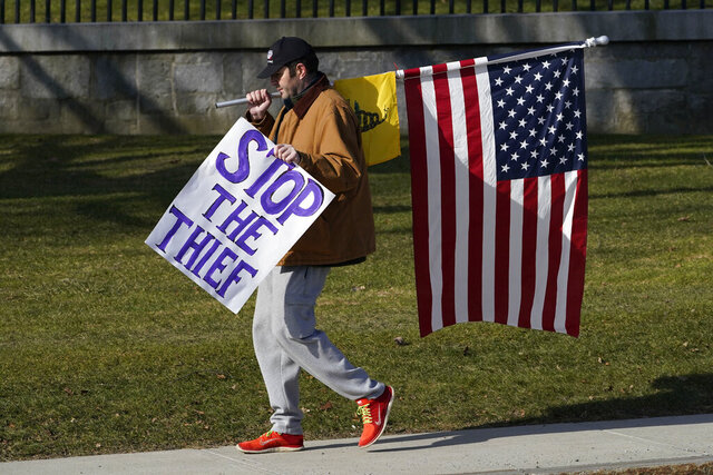 A protester walks in front of the Statehouse, Wednesday, Jan. 20, 2021, in Augusta, Maine. Law enforcement agencies stepped up patrols at the Statehouse to coincide with the inauguration of President Biden. (AP Photo/Robert F. Bukaty)
