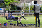 A personal trainer watches a client workout in a park in the eastern suburbs of Sydney Tuesday, Sept. 14, 2021. Personal trainers have turned a waterfront park at Sydney's Rushcutters Bay into an outdoor gym to get around pandemic lockdown restrictions. (AP Photo/Mark Baker)