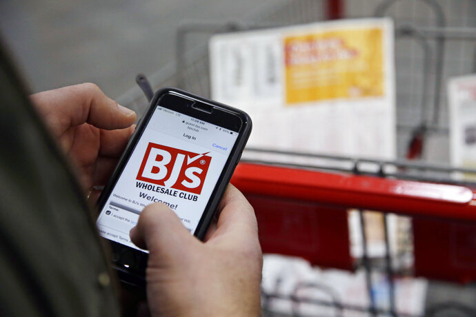 FILE- In this Feb. 13, 2018, file photo Tony D'Angelo logs into the stores Wi-Fi to download the BJ's Express Scan app on his cell phone before beginning his shopping at the BJ's Wholesale Club in Northborough, Mass. BJ's Wholesale Club is going public, again. BJ's has announced that it filed a form S-1 with the U.S. Securities and Exchange Commission for an initial public offering. (AP Photo/Stephan Savoia, File)