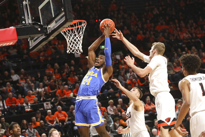 UCLA's Jalen Hill grabs a rebound away from Oregon State's Kylor Kelley (24) and Tres Tinkle (3) during the first half of an NCAA college basketball game in Corvallis, Ore., Sunday, Jan. 13, 2019. (AP Photo/Amanda Loman)