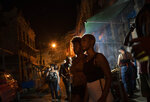 Women listen to a street performance by the Brazilian band Atitude Nossa as the restrictions related to the COVID-19 pandemic are eased in Rio de Janeiro, Brazil, Monday, Oct. 5, 2020. Since the beginning of October, live shows are now permitted in Rio de Janeiro. (AP Photo/Silvia Izquierdo)