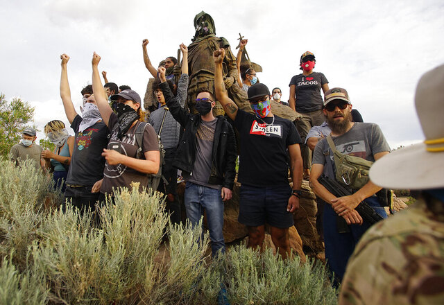 Demonstrators climb the statue of Don Juan de Onate in Old Town in Albuquerque, N.M., while an armed member of the New Mexico Civil Guard stands by during a protest calling for the removal of the likeness of the controversial New Mexico explorer Monday, June 15, 2020. (Adolphe Pierre-Louis/The Albuquerque Journal via AP)