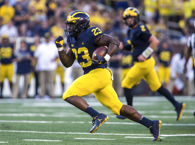 FILE - In this Sept. 15, 2018, file photo, Michigan running back O'Maury Samuels (23) rushes in the fourth quarter of an NCAA college football game against SMU, in Ann Arbor, Mich. Michigan dismissed running back O'Maury Samuels from its football program the same day he was arraigned on two charges, including one for domestic violence. The school did not say why the move was made Wednesday, Dec. 12, 2018, when Samuels was charged with domestic violence and malicious destruction of personal property. (AP Photo/Tony Ding, File)