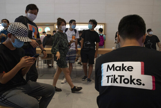 A visitor to an Apple store wears a t-shirt promoting Tik Tok in Beijing on Friday, July 17, 2020. U.S. President Donald Trump on Thursday, Aug 6, 2020 ordered a sweeping but unspecified ban on dealings with the Chinese owners of consumer apps TikTok and WeChat, although it remains unclear if he has the legal authority to actually ban the apps from the U.S. (AP Photo/Ng Han Guan)