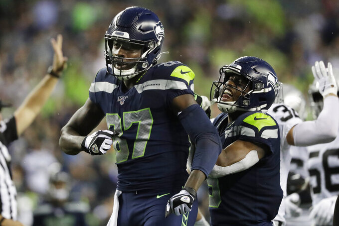 Seattle Seahawks wide receiver Jazz Ferguson (87) celebrates with wide receiver Terry Wright, right, after making a 41-yard catch during the first half of an NFL football preseason game against the Oakland Raiders, Thursday, Aug. 29, 2019, in Seattle (AP Photo/Elaine Thompson)