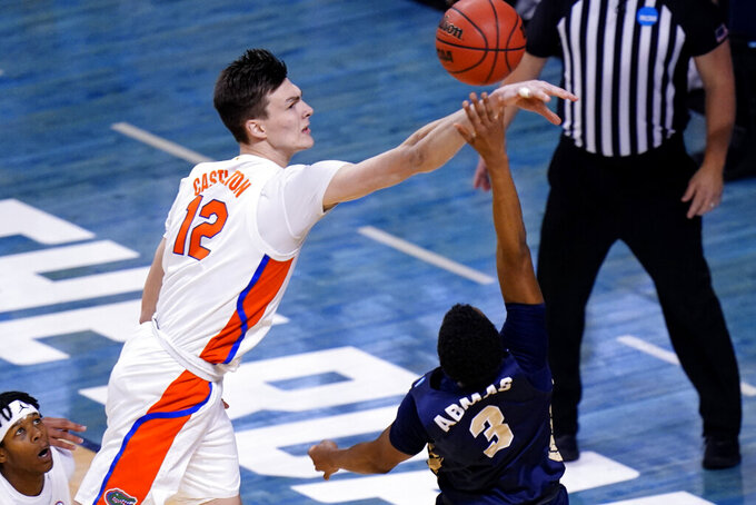 Florida forward Colin Castleton (12) blocks a shot by Oral Roberts guard Max Abmas (3) during the second half of a college basketball game in the second round of the NCAA tournament at Indiana Farmers Coliseum, Sunday, March 21, 2021 in Indianapolis. (AP Photo/AJ Mast)