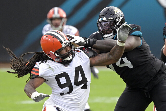 Jacksonville Jaguars offensive tackle Cam Robinson, right, blocks Cleveland Browns defensive end Adrian Clayborn (94) on a play during the second half of an NFL football game, Sunday, Nov. 29, 2020, in Jacksonville, Fla. (AP Photo/Phelan M. Ebenhack)