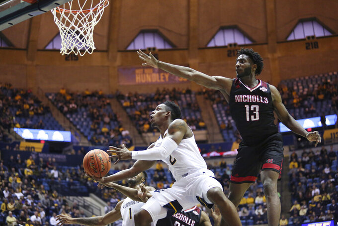 West Virginia guard Brandon Knapper (2) is defended by Nicholls State guard Andre Jones (13) as he goes to make a shot during the second half of an NCAA college basketball game Saturday, Dec. 14, 2019, in Morgantown, W.Va. (AP Photo/Kathleen Batten)