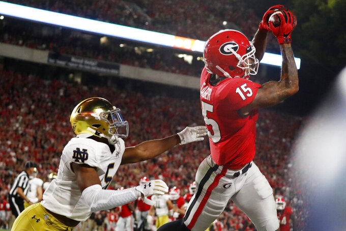 Georgia wide receiver Lawrence Cager (15) makes a catch for a touchdown against Notre Dame cornerback Troy Pride Jr. (5) during the second half of an NCAA college football game, Saturday, Sept. 21, 2019, in Athens, Ga. Georgia won 23-17. (AP Photo/John Bazemore)