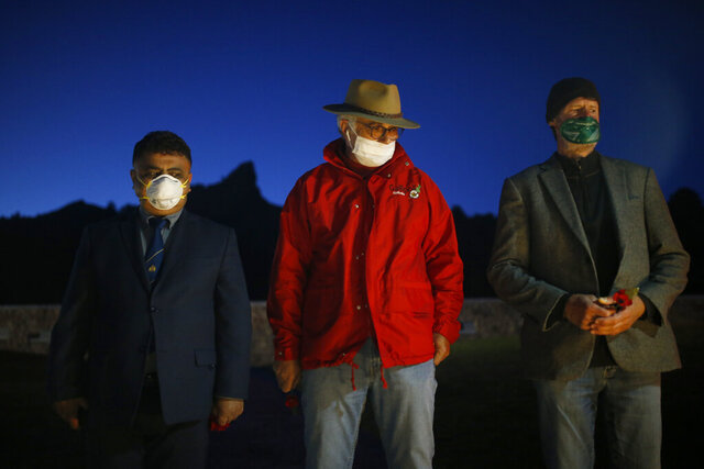 Employees of a local tourism company, wearing face masks as a preventive measure against the spread of the new coronavirus, stand in attention as they pay their respects at the Anzac Cove beach memorial in Gallipoli peninsula, the site of World War I landing of the ANZACs (Australian and New Zealand Army Corps) on April 25, 1915, in Canakkale, Turkey, early Saturday, April 25, 2020. The dawn service ceremony and all other commemorative ceremonies honoring thousands of Australians and New Zealanders who fought in the Gallipoli campaign of World War I on the ill-fated British-led invasion, were cancelled this year due to the new coronavirus pandemic. (AP Photo/Emrah Gurel)