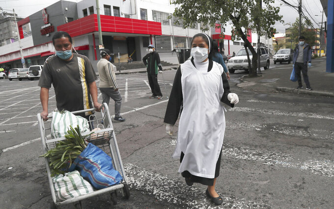 A nun, wearing a protective face mask and disposable gloves as a precaution against the spread of the new coronavirus, and a worker carting her groceries, walk to a waiting taxi in Quito, Ecuador, Saturday, March 28, 2020. The government has declared a health emergency, enacting a curfew and restricting movement to only those who provide basic services. (AP Photo/Dolores Ochoa)
