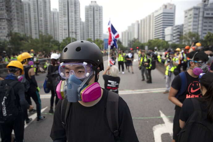 """In this Aug. 16, 2019, photo, Wayne, a 33-year-old self-described """"front line"""" protester, stands along with other demonstrators in Tai Po, on Hong Kong's outskirts. Hong Kong's protest movement has reached a moment of reckoning after protesters occupying the airport held two mainland Chinese men captive, and pro-democracy lawmakers and fellow demonstrators question whether the whole operation has gone too far. (AP Photo/Vincent Thian)"""