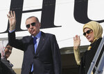 Turkish President Recep Tayyip Erdogan and his wife Emine Erdogan wave as they board a plane before a visit to the United States, in Ankara, Turkey, Tuesday, Nov. 12, 2019. Erdogan warned European nations Tuesday that his country could release all the Islamic State group prisoners it holds and send them to Europe, in response to EU sanctions over Cyprus.(Presidential Press Service via AP, Pool)