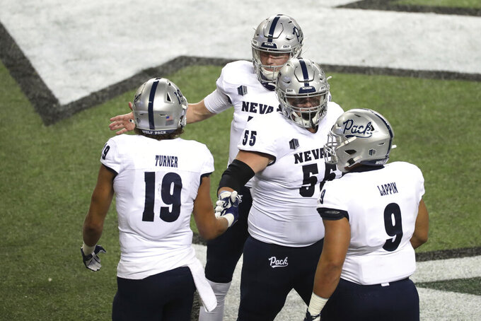 Nevada tight end Cole Turner (19) celebrates with teammates, including offensive lineman Tyler Orsini (55) and quarterback Carson Strong, after scoring a touchdown against Hawaii during the first half of an NCAA college football game Saturday, Nov. 28, 2020, in Honolulu. (AP Photo/Marco Garcia)