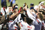Liberty players celebrate with the trophy after defeating Coastal Carolina in overtime in the Cure Bowl NCAA college football game Saturday, Dec. 26, 2020, in Orlando, Fla. (AP Photo/Matt Stamey)