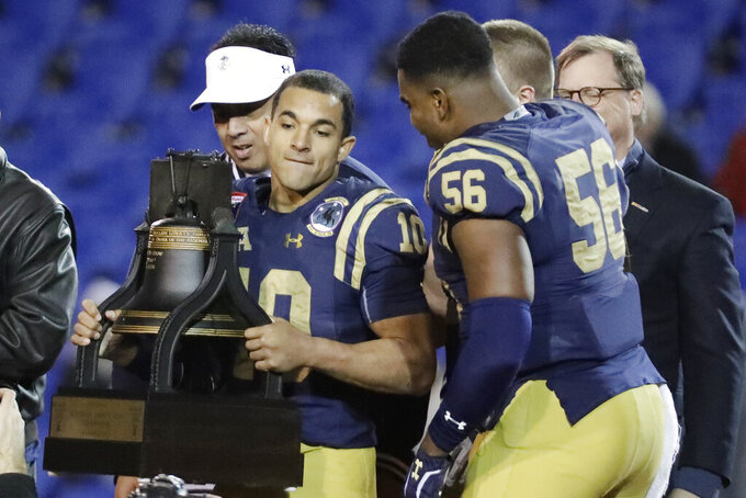 Navy quarterback Malcolm Perry (10) holds the trophy after Navy beat Kansas State in the Liberty Bowl NCAA college football game Tuesday, Dec. 31, 2019, in Memphis, Tenn. Navy won 20-17. (AP Photo/Mark Humphrey)