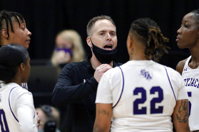 Stephen F. Austin head coach Mark Kellogg talks with his players during the second half of an NCAA college basketball game against Sam Houston State for the Southland Conference women's tournament championship Sunday, March 14, 2021, in Katy, Texas. (AP Photo/Michael Wyke)
