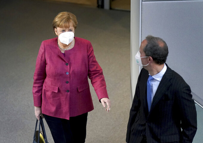 German Chancellor Angela Merkel, left, arrives for a meeting of the German federal parliament, Bundestag, at the Reichstag building in Berlin, Germany, Wednesday, April 21, 2021. (AP Photo/Michael Sohn)