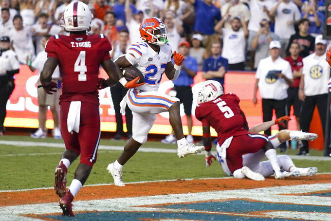Florida running back Dameon Pierce (27) goes past Florida Atlantic safety Teja Young (4) and linebacker Ahman Ross (5) for a touchdown during the first half of an NCAA college football game Saturday, Sept. 4, 2021, in Gainesville, Fla. (AP Photo/John Raoux)