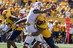 FILE - In this Sept. 14, 2019, file photo, West Virginia defensive lineman Dante Stills (55) sacks North Carolina State quarterback Matthew McKay (7) during the second half of an NCAA college football game in Morgantown, W.Va. Dante Stills and his older brother, Darius, are among the Big 12's sack leaders and they'll be looking to cause more disruption when West Virginia hosts No. 11 Texas on Saturday. They  are the sons of former all-Big East and NFL Pro Bowl linebacker Gary Stills. (AP Photo/Raymond Thompson, File)