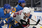 St. Louis Blues' Jake Walman, left, chases after a loose puck along with teammate Justin Faulk (72) and Arizona Coyotes' John Hayden, right, during the third period of an NHL hockey game Saturday, Feb. 6, 2021, in St. Louis. (AP Photo/Jeff Roberson)