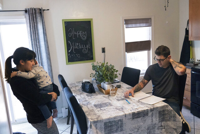 Comedian Brad Pierce, right, looks over the notebook us uses to write jokes as he sits in the kitchen next to his wife, Carmen, and their nephew, Maddox, 1, in West Warwick, R.I., Friday, Jan. 8, 2021. Pierce was finally doing well with his comedy when the pandemic hit. Now he wonders if he can possibly build up his career again. He has a friend who drives for Amazon and fears having to get a job like that while talking about the good old days when he was an entertainer. (AP Photo/David Goldman)