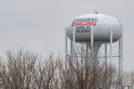 The water tower for the town of Speedway, Ind., proclaims itself the Racing Capital of the World outside the grounds of the Indianapolis Motor Speedway in Indianapolis, Saturday, March 28, 2020. Roger Penske, at 83 and considered high risk to the coronavirus as a 2017 kidney transplant recipient, still makes the daily three-minute commute to his Bloomfield Hills, Mich, office. He works 12 or more hours a day from his conference room at Penske Corp., which has a skeleton crew all practicing social distancing. Penske also had the small matter of planning his first Indianapolis 500.  (AP Photo/Michael Conroy)