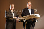In this Dec. 2, 2013, file photo US Airways president Scott Kirby, left, and chairman and CEO Doug Parker pose for a photo at the airline's headquarters in Phoenix, Ariz. United announced Thursday, Dec. 5, 2019, that CEO Oscar Munoz will step down in May and be succeeded by Kirby, currently the airline's president. Kirby left American Airlines in mid-2016 in what the company described as part of its long-term succession planning. In effect, Kirby was passed over as the heir apparent to CEO Doug Parker in favor of Robert Isom, then American's chief operating officer. (Tom Fox/The Dallas Morning News via AP)