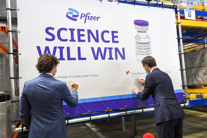 Canada's Prime Minister Justin Trudeau, left, and Belgium's Prime Minister Alexander De Croo, right, sign a banner during a working visit to the Pfizer pharmaceutical company in Puurs, Belgium, Tuesday, June 15, 2021. Canadian Prime Minister Justin Trudeau paid a visit to the Belgian Pfizer factory on Tuesday to thank employees making the COVID-19 vaccine. (Frederic Sierakowski, Pool via AP)