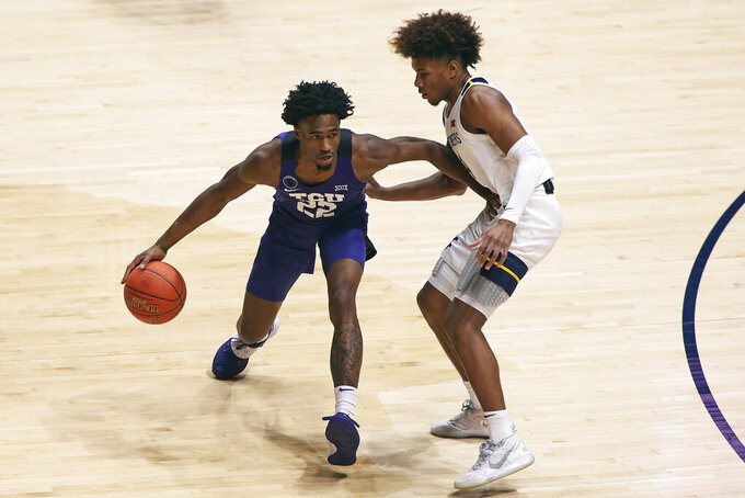 TCU guard RJ Nembhard (22) is defended by West Virginia guard Miles McBride (4) during the first half of an NCAA college basketball game Thursday, March 4, 2021, in Morgantown, W.Va. (AP Photo/Kathleen Batten)