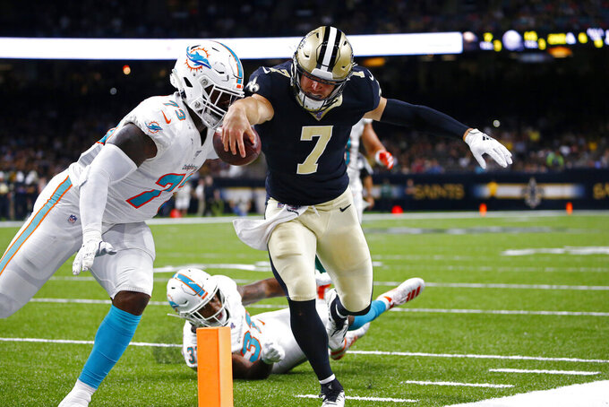 New Orleans Saints quarterback Taysom Hill (7) tries in vain to cross the pylon as he carries against Miami Dolphins defensive end Dewayne Hendrix (73) in the second half of an NFL preseason football game in New Orleans, Thursday, Aug. 29, 2019. (AP Photo/Butch Dill)